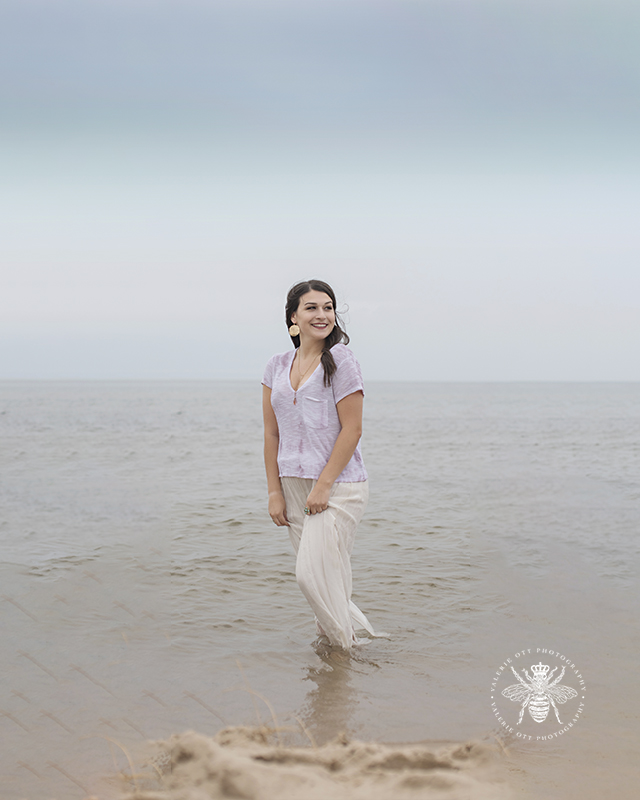 senior girl wears a flowing top and pants and wades in the water of a beach