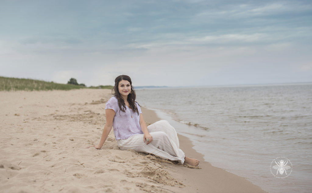 senior girl poses on beach wearing flowing pants and top