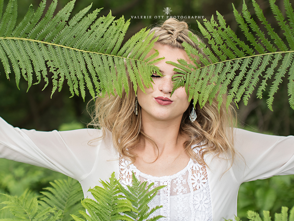 senior girl wears white top with her half up and hides her eyes behind some green plants