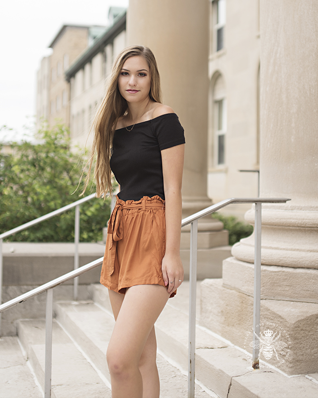 senior girl poses in black top and orange shorts on steps