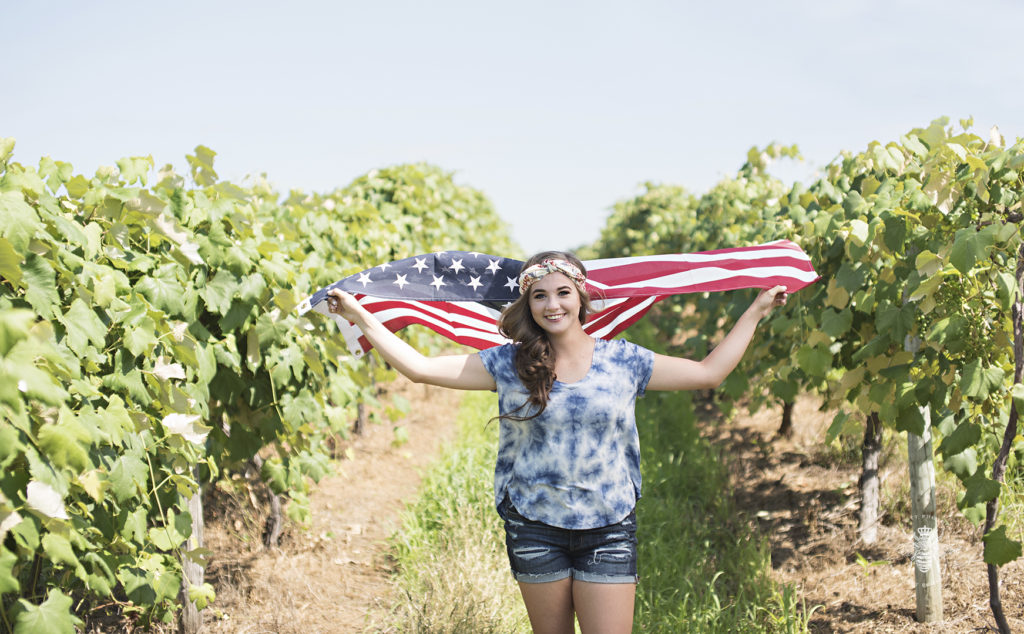 senior girl runs through a vineyard with the wind blowing through an American flag. She wears denim shorts and a blue tie dye shirt.