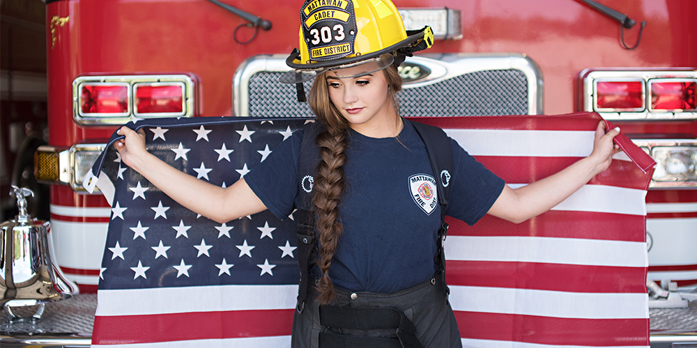 senior girl poses in Mattawan fire truck wearing her fire fighter uniform and holding up an American flag
