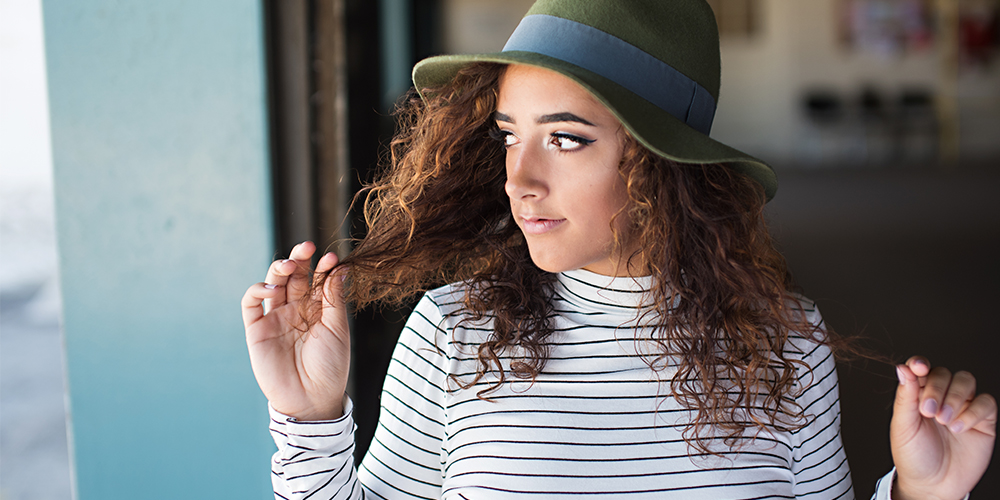 senior girl poses in a black and white striped turtleneck and a green hat