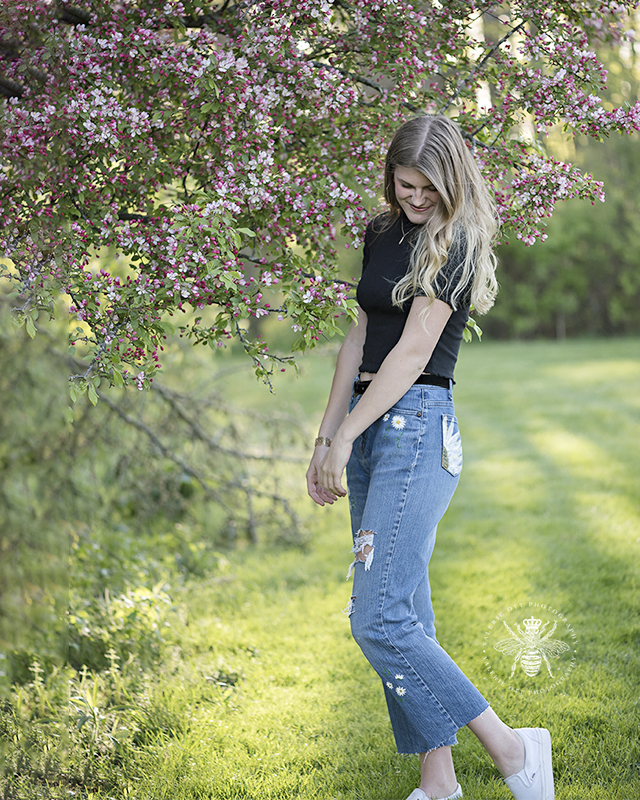 west michigan senior girl, a member of valerie's bee squad, poses among the blossoming redbuds. She wears jeans with handpainted flowers on them.