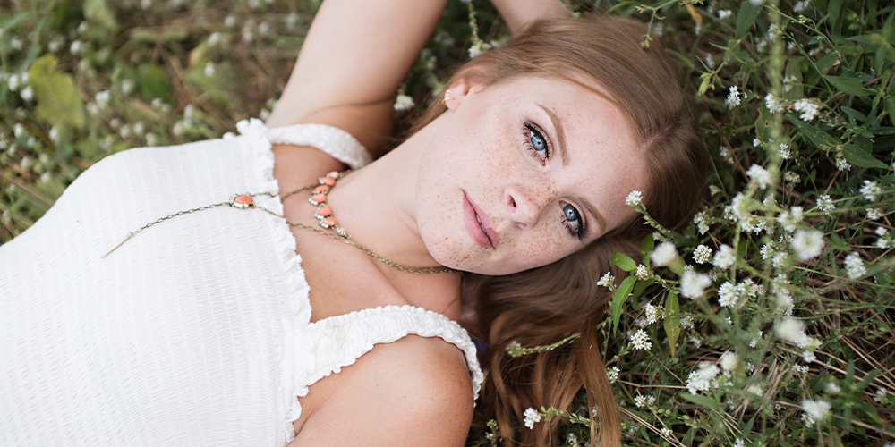 Portage Central senior lays in flowers and looks up. She wears a white top that matches the flowers