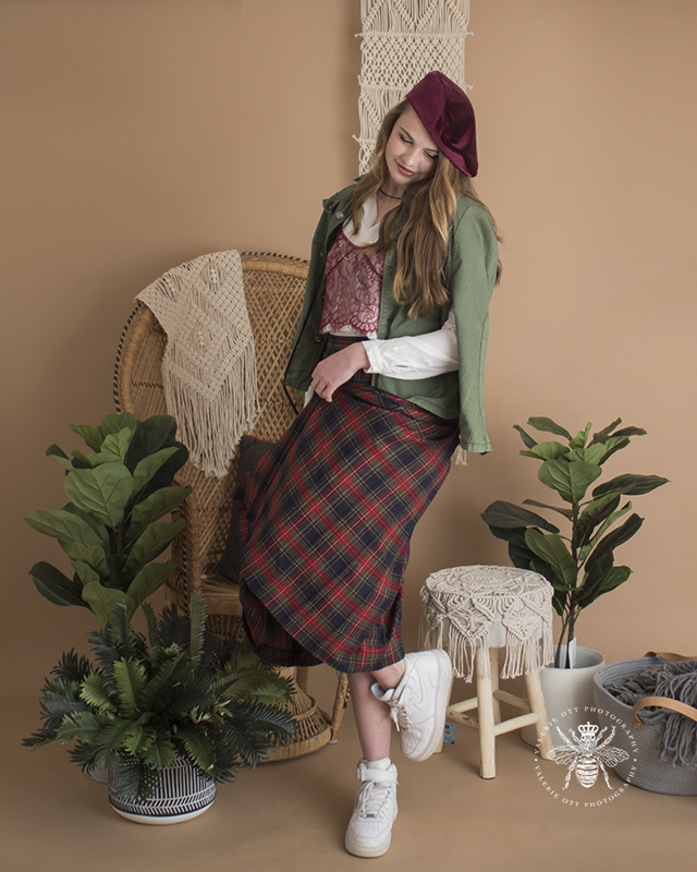 West Michigan senior girl poses in a studio with plants and a vintage background. Mix and match clothes, she wears a red beret, a green jacket, a red lace tank top layered over a white shirt, a green and red plaid skirt, and white tennis shoes.