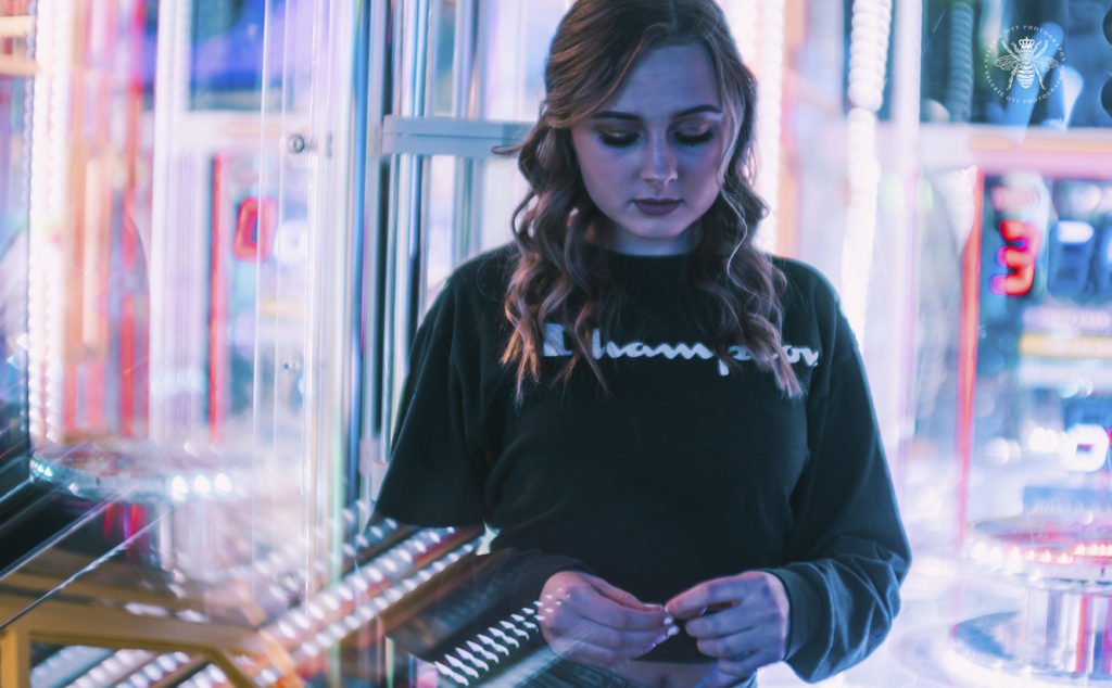 West Michigan senior girl poses by arcade games in Revel and Roll with the bright lights surrounding her.
