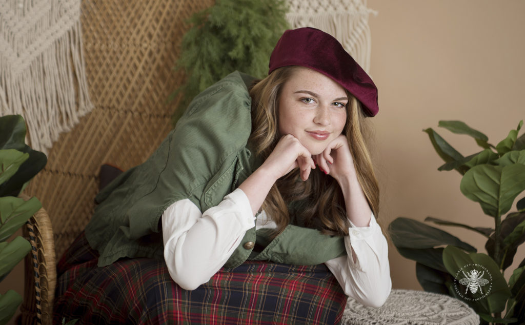 West Michigan senior girl poses in a studio with plants and a vintage background. Mix and match clothes, she wears a red beret, a green jacket, a green and red plaid skirt. She poses on a vintage chair.