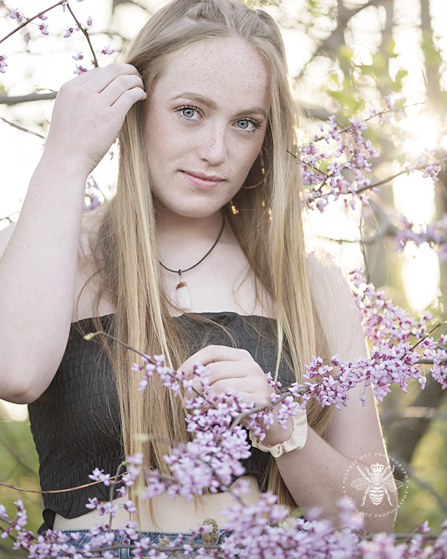 west michigan senior girl, a bee squad member, poses among the blossoming redbuds