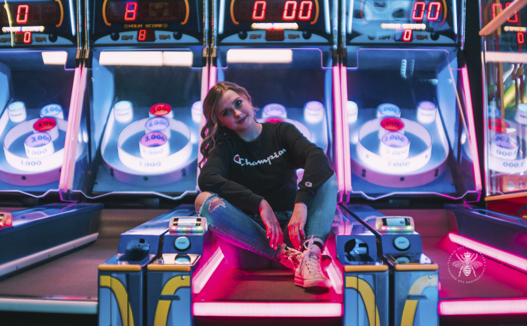 West Michigan senior girl poses by arcade games in Revel and Roll with the bright lights surrounding her. She wears ripped jeans, converse, and a Champion sweatshirt.