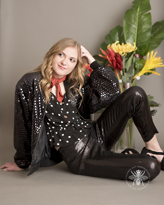 West Michigan senior session. Senior is daring with her style, and she wears a black sequin jacket, black sequin pants, a rust colored scarf, and a black and white polka dot top. She poses with red and yellow flowers in front of a gray background.