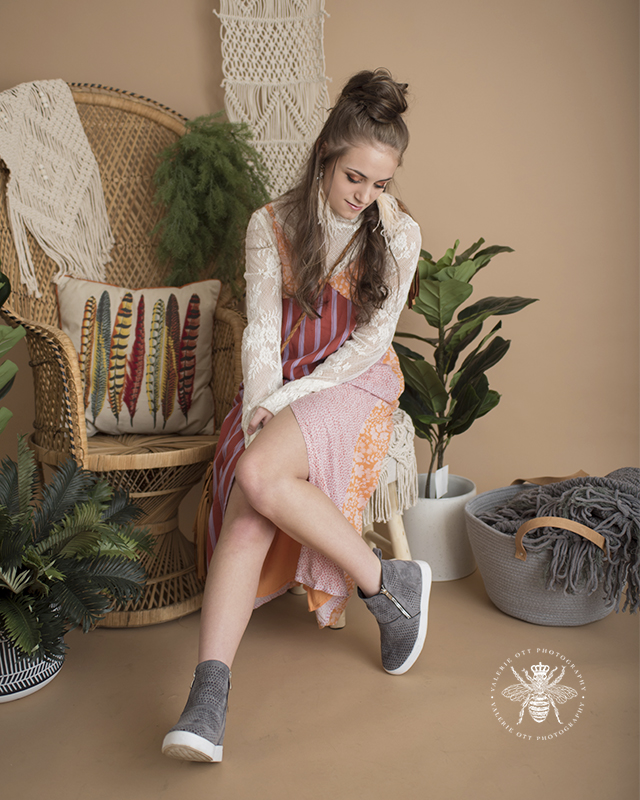 Mattawan senior girl poses in a studio with a vintage background with plants. She wears her hair half up, feather earrings, an orange, red and purple striped sundress layered over a white lace high neck top, and she wears gray wedge sneakers.
