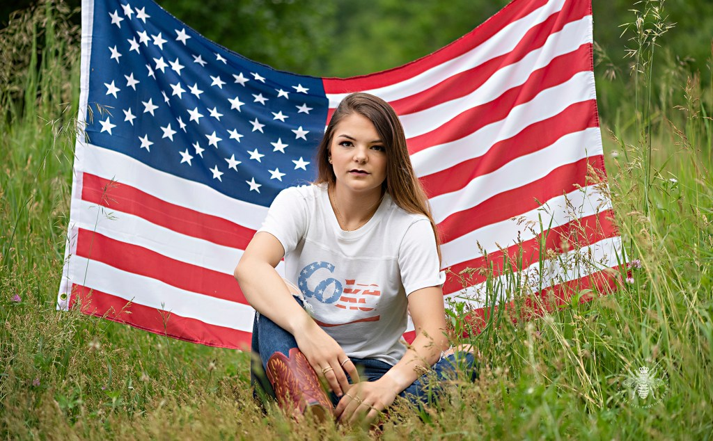 Mattawan senior girl poses in front of an American flag wearing a patriotic Coke t shirt, jeans, and cowboy boots.
