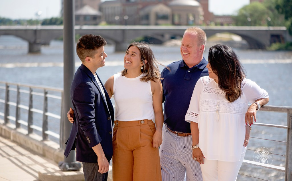 West Michigan family photos. Family members pose in orange, navy, white, and gray colors. They pose in front of a bridge over the water.