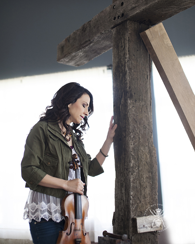 Photo session with Irish worship singer. She poses with her violin and leans against a cross.