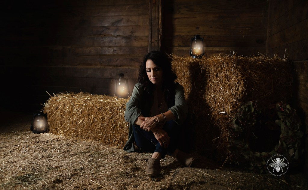 Album cover for Irish singer shot in a barn. She sits next to a haystack with lanterns around her.