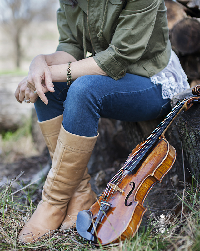 Photo session with Irish singer. She sits on a tree stump with her violin leaning against it.