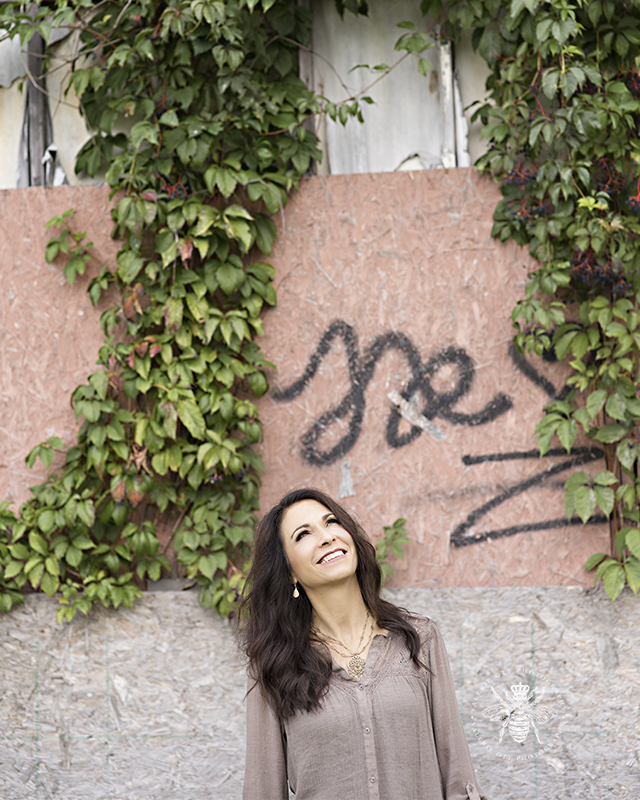 Photo session with Irish singer. She poses in front of a graffiti and vine covered wall.