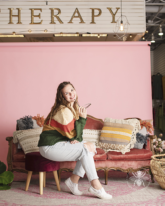 Model poses in front of pink background and vintage couch at Therapy Boutique in Portage, MI. She wears a peach, beige, green, and yellow colorblock sweater. She holds a pair of sunglasses.