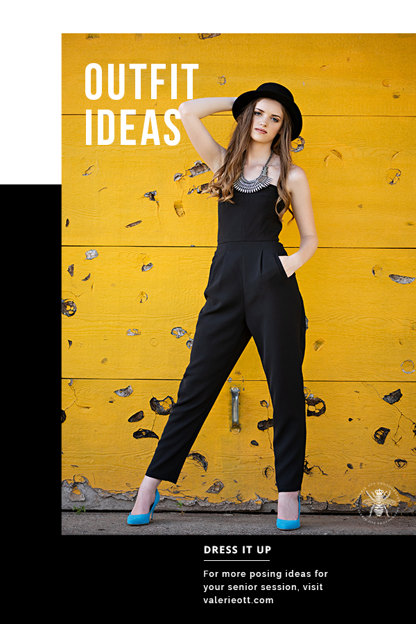 Senior girl poses in front of a yellow wall. She wears a black hat, black jumpsuit, and bright blue heels.Text reads: outfit ideas, dress it up, for more posing ideas for your senior session, visit valerieott.com