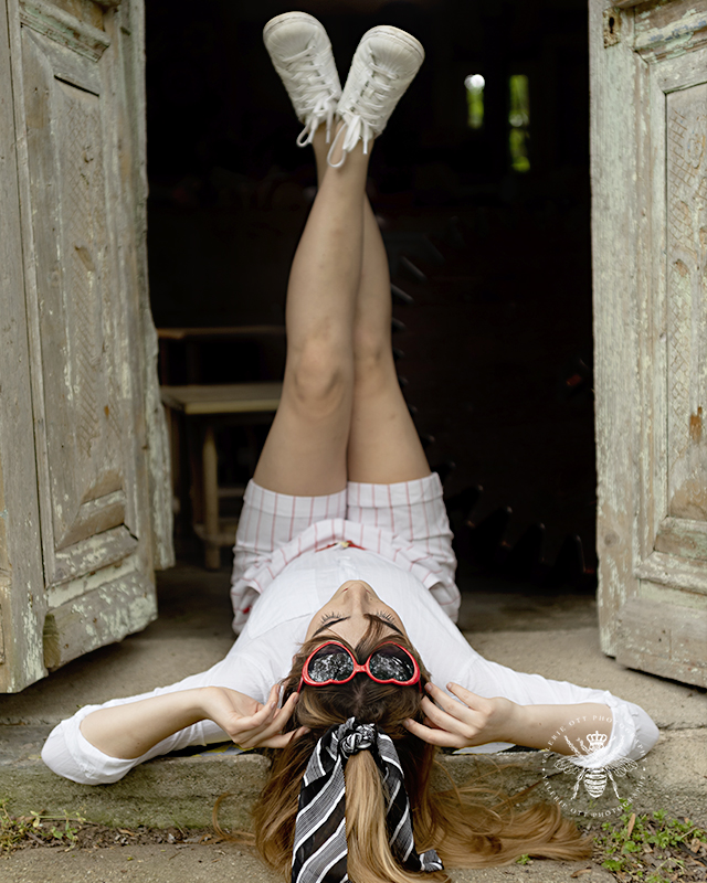 Mattawan senior girl poses in a doorway laying with her feet up. She wears red striped shorts, sneakers, red heart sunglasses, and a striped hair scarf.