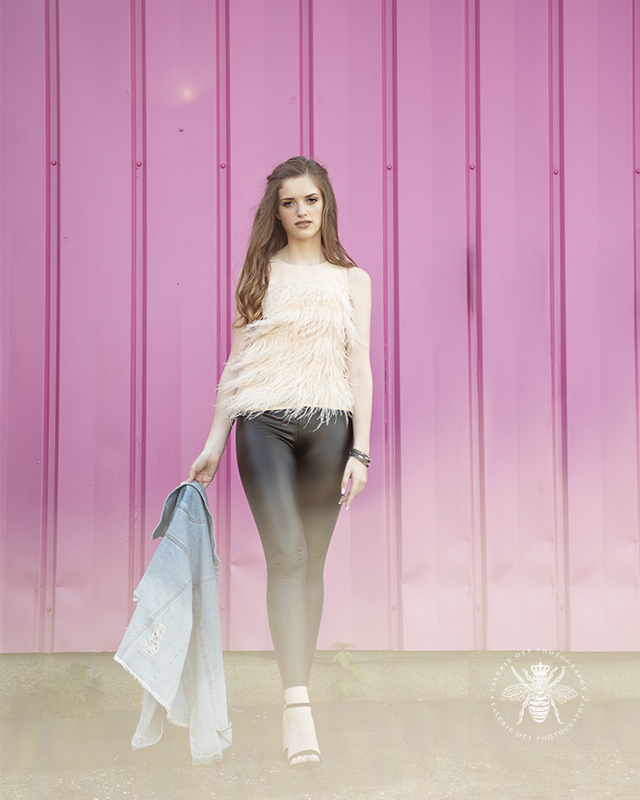 Senior girl poses in front of a bright pink wall. She wears a light pink fringe top and lack leather leggings. She also carries a denim jacket.