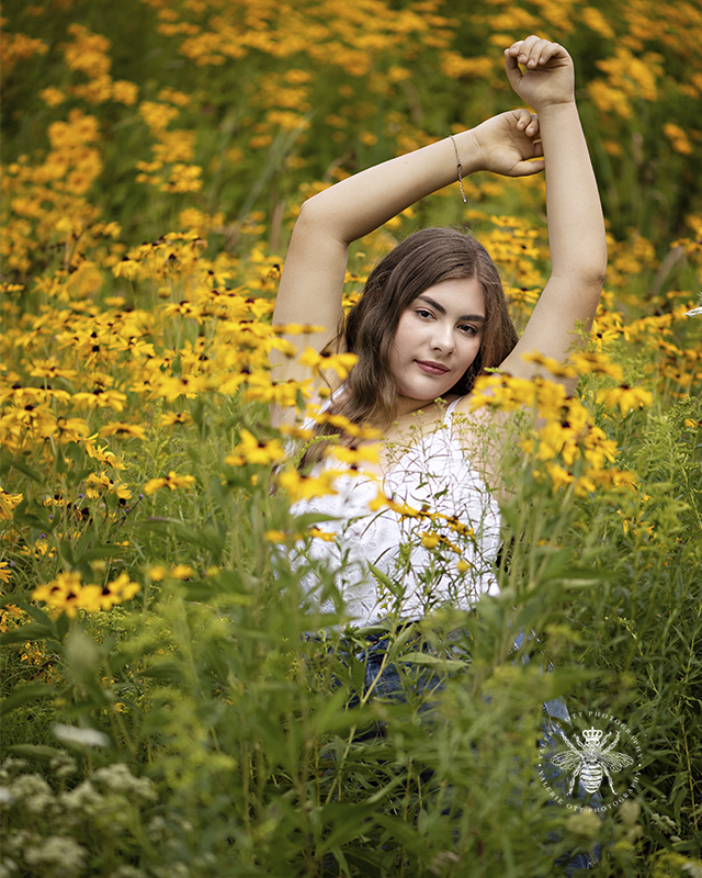 West Michigan giveaway winner senior girl poses with her arms abover her head in a field of yellow flowers. She wears a white tank top