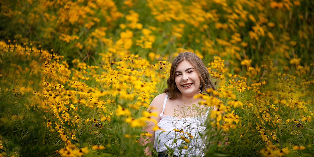 West Michigan senior girl poses in a field of yellow flowers. She wears a white tank top.