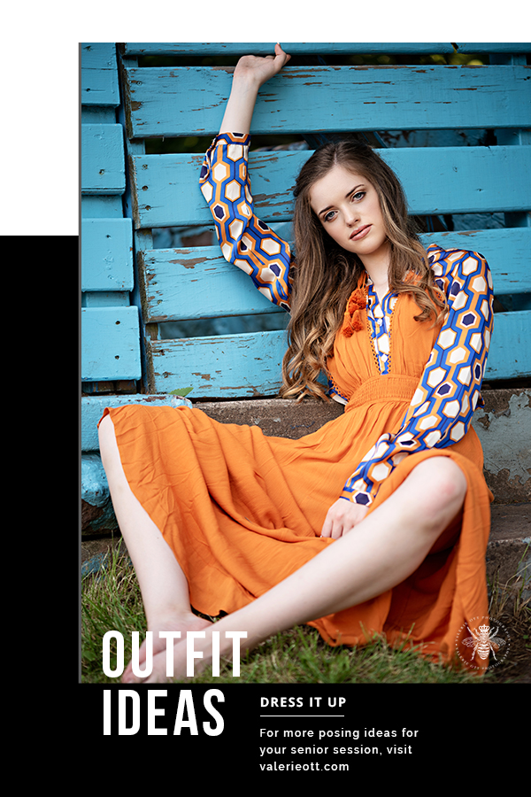 Senior girl poses in front of a blue wall. She wears an orange dress layered over a retro blue and orange patterned top. Text reads: outfit ideas, dress it up, for more posing ideas for your senior session, visit valerieott.com
