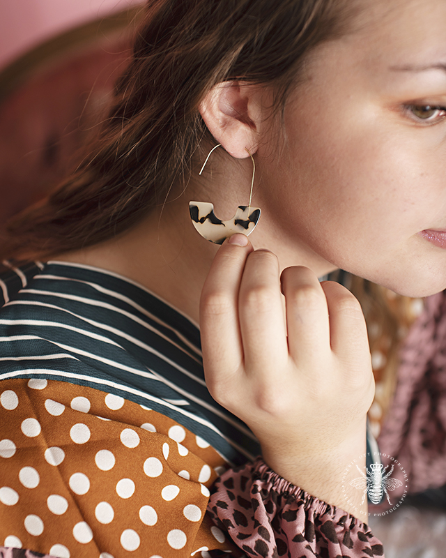 Model wears leopard print earrings and a funky patterned top in Therapy Boutique in Portage, MI.