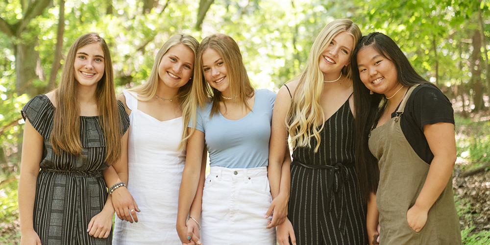 Kalamazoo Christian BFF session. Senior girls wear black, white, blue, and brown colors. They pose with their arms linked in a forest in West Michigan.