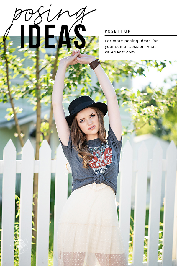 Senior girl poses in front of a white picket fence. She lifts her arms above her head. She wears a t shirt knotted in front with a statement necklace layered over a white dress. Text reads: posing ideas, pose it up, for more posing ideas for your senior session, visit valerieott.com