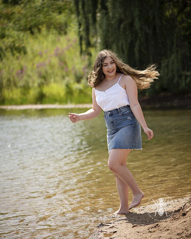 West Michigan giveaway winner senior girl dances along the beach of a lake. She wears a denim skirt, a white tank top, and she's barefoot. Her long brown hair flows behind her.