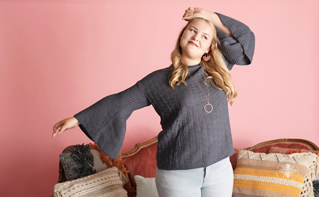 Model poses in front of a pink background and a vintage couch. She wears a blue bell sleeved sweater, pink statement earrings, and a long necklace.