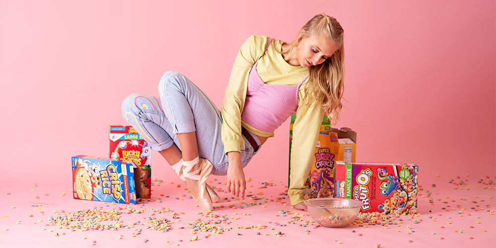 Western Michigan University dancer poses in painted jeans and ballet slippers. She poses in front of a pink background with cereal.