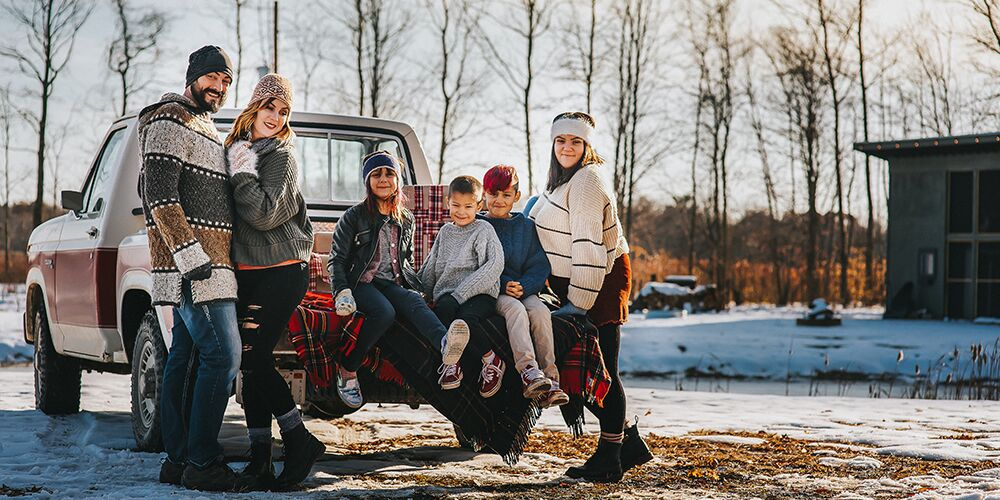 Mini Christmas family session at The Fields of Michigan. Family poses together on a truck.
