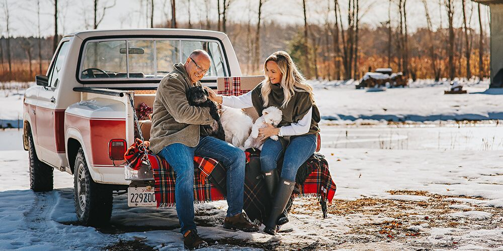 Christmas mini sessions at The Fields of Michigan. Couple poses with their dogs on the back of a truck with a plaid blanket.