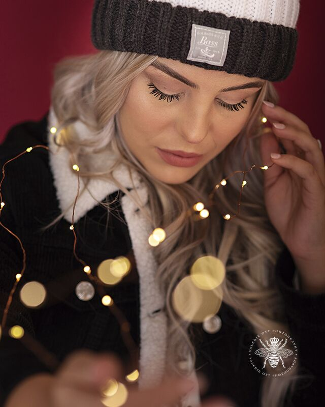 Western Michigan University senior session. Senior poses with a firefly lights in a studio in front of a red backdrop. She wears a black and white jacket and a beanie.