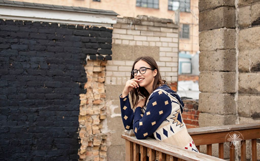Loy Norrix girl poses leaning against a balcony. She wears glasses and a sweater.