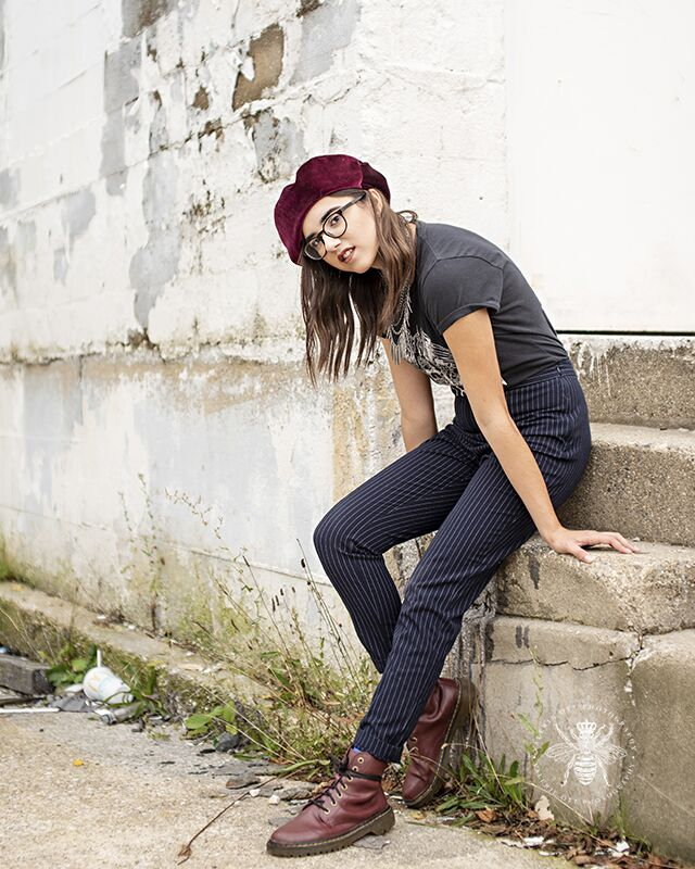 Loy Norrix senior girl poses kneeling on a step. She wears a red velvet beret, glasses, and layered necklaces.