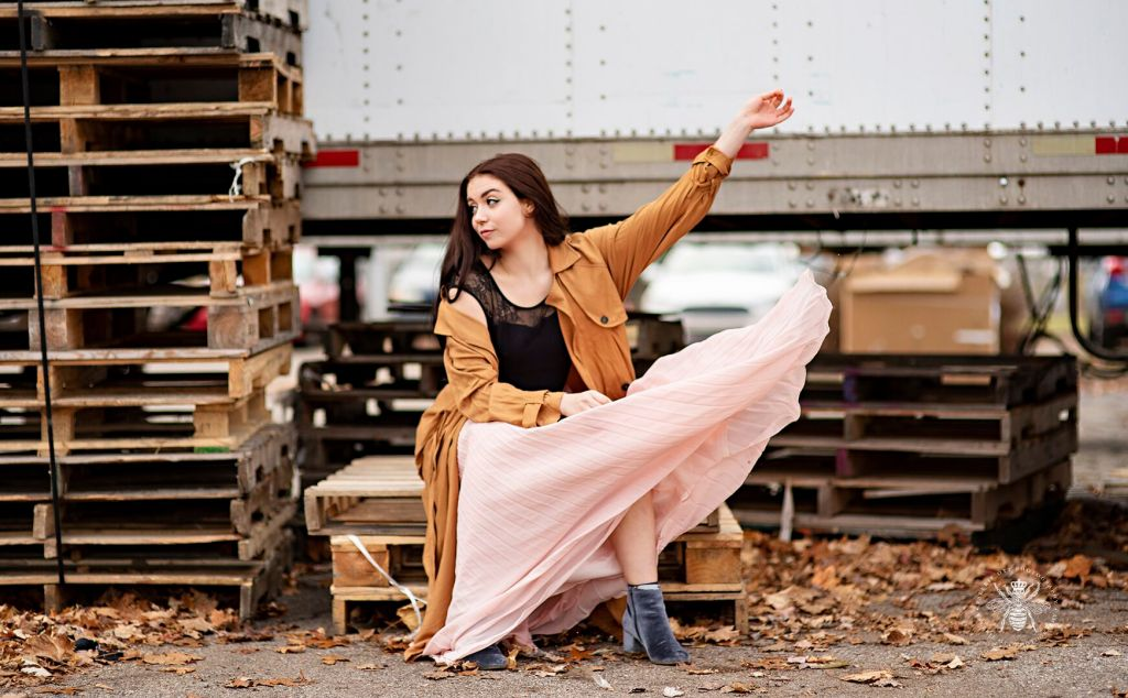 Dancer at Western Michigan University dances among empty crates and wears a flowing pink skirt and a long jacket.