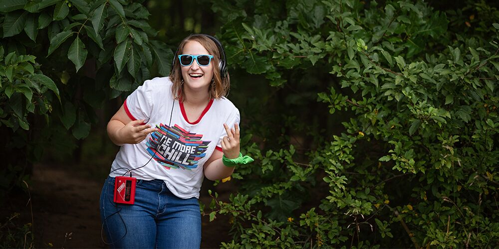 Mattawan senior pics in the woods on a rainy day. Senior girl wears a vintage cassette player and headset and a Be More Chill Musical t shirt.