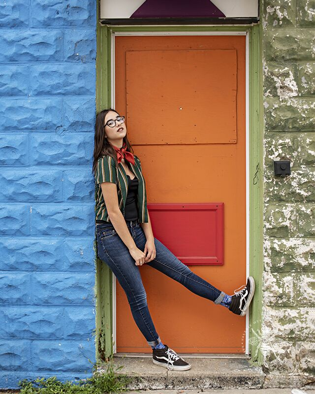 High School girl poses leaning against a colorful doorway. She wears glasses, a striped top, and a red ascot.