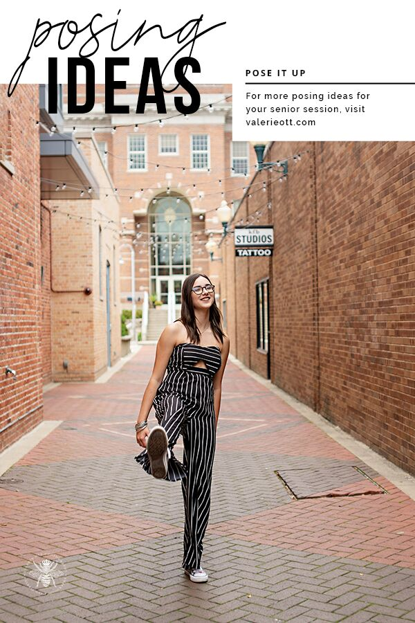 Loy Norrix senior girl poses kicking her leg out in an alley. She wears glasses and a striped jumpsuit. Text reads: posing ideas, pose it up, for more posing ideas for your senior session, visit valerieott.com