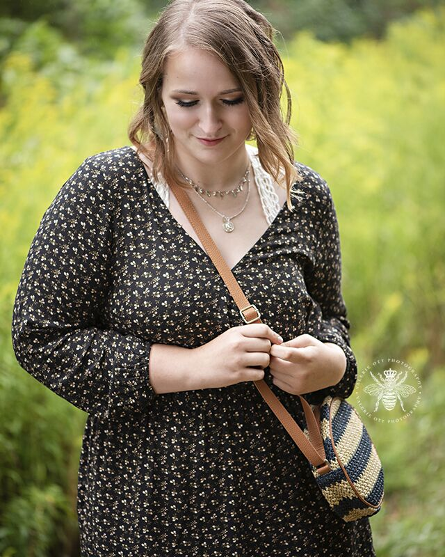 Mattawan senior poses in a field. She wears a black floral dress and a crossbody purse.