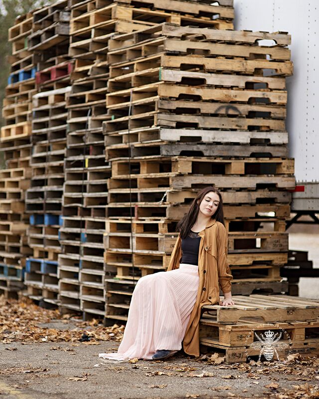 Western Michigan University dances among empty crates and wears a flowing pink skirt and a long jacket.