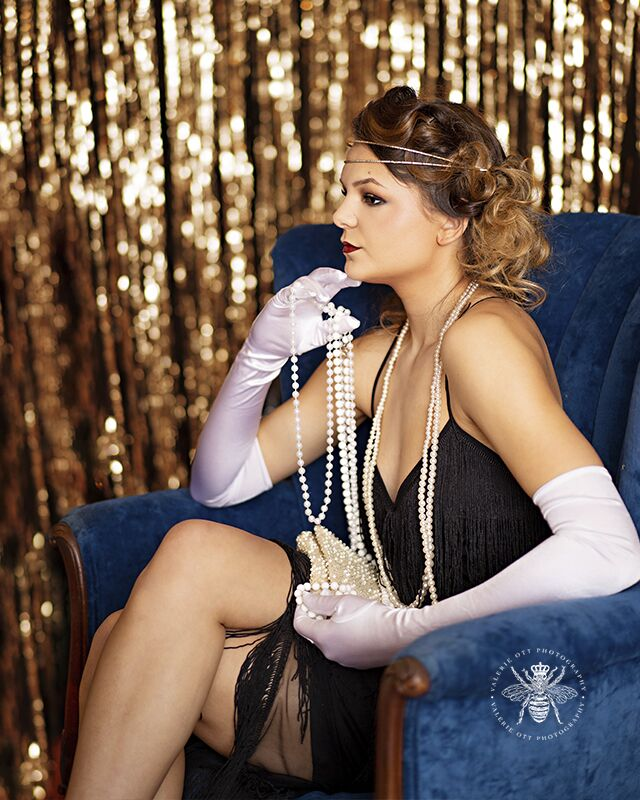 Mattawan senior poses for styled session in West Michigan. She wears her hair in pin curls, red lipstick, white gloves, pearl necklaces, and a flapper dress. She poses sitting in a blue velvet chair in front of a shimmering gold background.