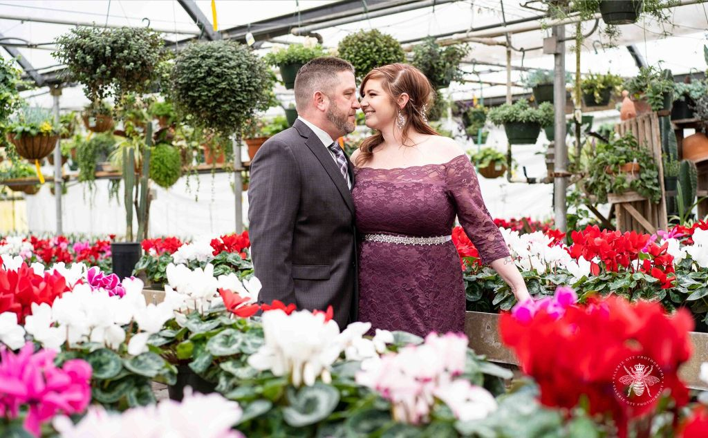 Couple poses embracing in a greenhouse. The bride wears a long, purple lace dress with a silver belt around her waist. The groom wears a suit and patterned tie.