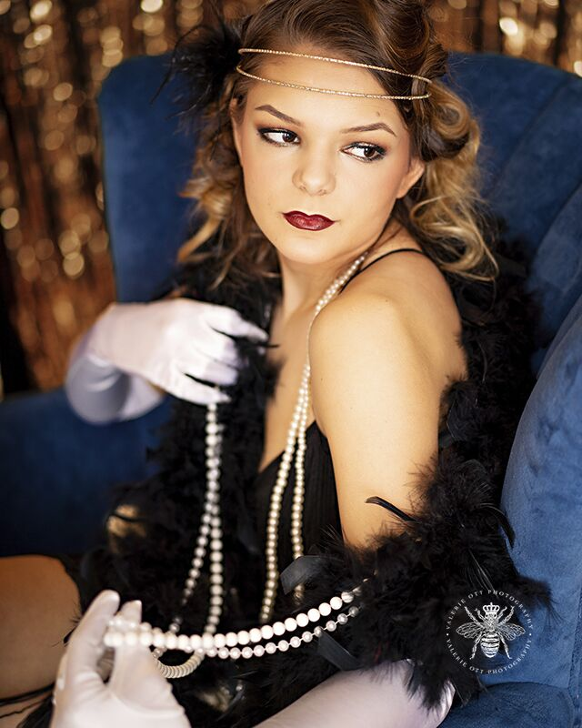 Mattawan senior poses in West Michigan. She wears her hair in pin curls, red lipstick, white gloves, pearl necklaces, a feather boa, and a flapper dress. She poses sitting in a blue velvet chair in front of a shimmering gold backdrop.