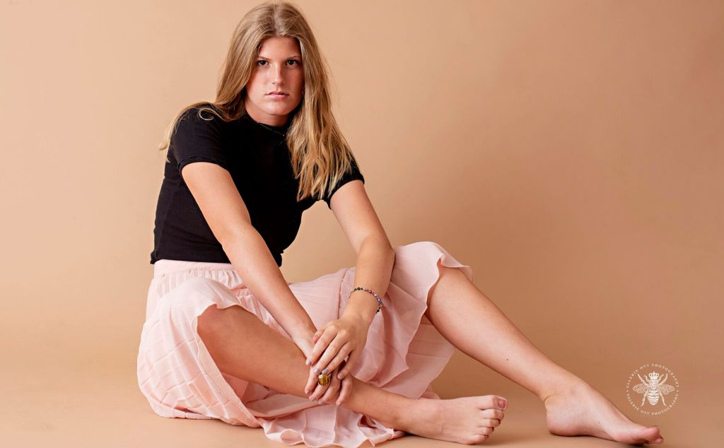 Model poses sitting in a studio wearing a long light pink pleated skirt and a black top.